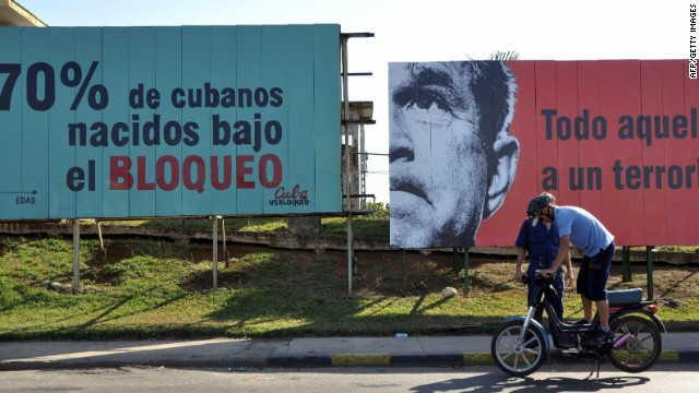 A Cuban checks his motorcycle in front of billboards alluding to the U.S. embargo on Cuba, on April 20, 2009 in Havana.